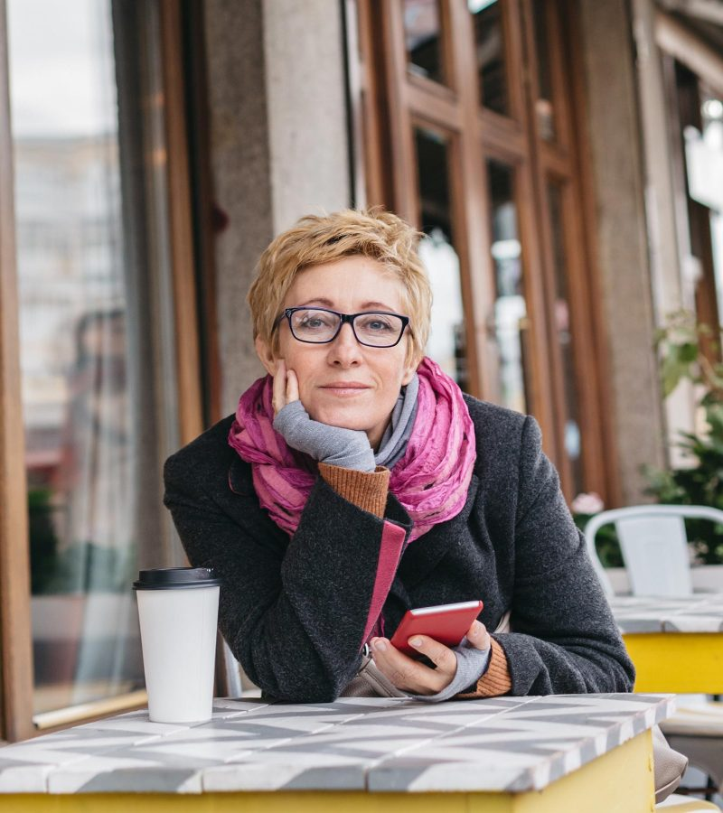 dreamy-woman-with-phone-in-cafe-PMSP74W.jpg